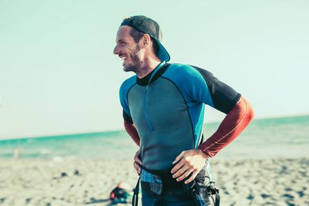 Smiling Caucasian man kitesurfer on the beach