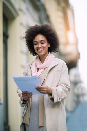 Mixed-raced woman holding document outdoor Stock Photo