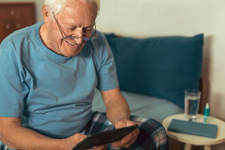 Senior man using digital tablet. Surprised mature male using portable computer at home