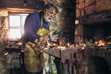 De smid smeedt handmatig het gesmolten metaal op het aambeeld in smederij met vonkvuurwerk