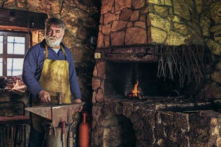 Senior blacksmith forge iron at work