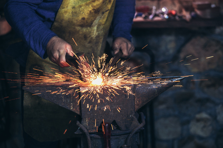 The blacksmith manually forging the molten metal on the anvil in smithy with spark fireworks, close up Stock Photo