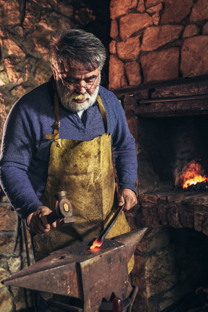 Senior blacksmith forge iron at work