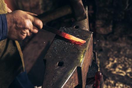 The blacksmith manually forging the molten metal