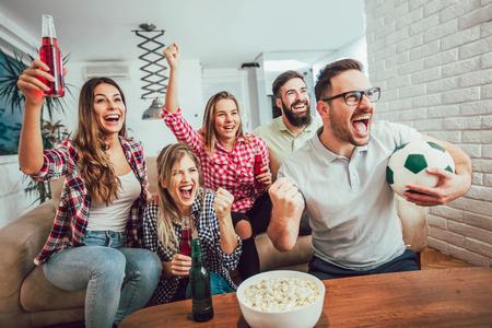 Amigos felices o fanáticos del fútbol que ven fútbol en la televisión y celebran la victoria en casa. Concepto de amistad, deportes y entretenimiento.