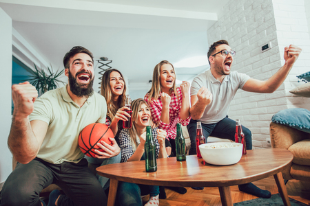 Happy friends or basketball fans watching basketball game on tv and celebrating victory at home.Friendship, sports and entertainment concept. Imagens - 93317739