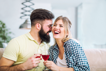 Photo of a young cheerful couple toasting at home with wine. Stock Photo