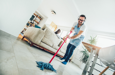 Concepto de limpieza y limpieza del marido. Un hombre limpia la casa, mientras las mujeres chismean en el sofá Foto de archivo
