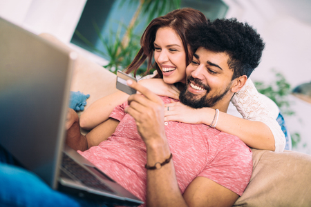 Happy interracial couple shopping online at home, using credit card, laughing