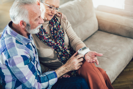 Seniors couple at home measuring blood pressure. Home monitoring Reklamní fotografie - 93744769