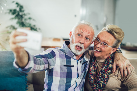 Happy senior couple sitting together on a sofa in their living room at home smiling and taking a selfie with a phone