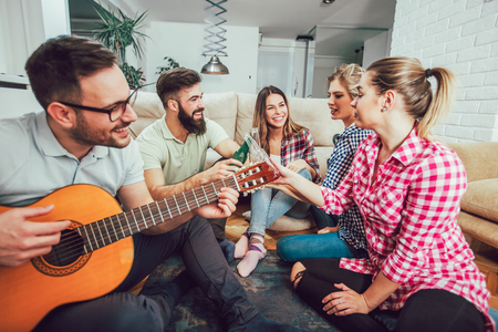 Group of happy young friends having fun and drinking beer in home interior Stock Photo