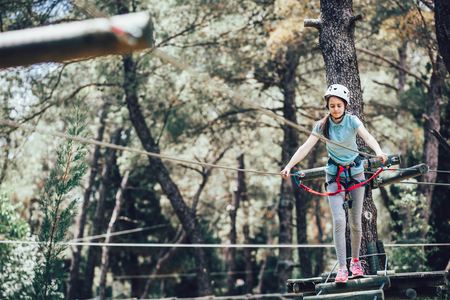 Happy school girl enjoying activity in a climbing adventure park on a sunny day Stock fotó - 94123675