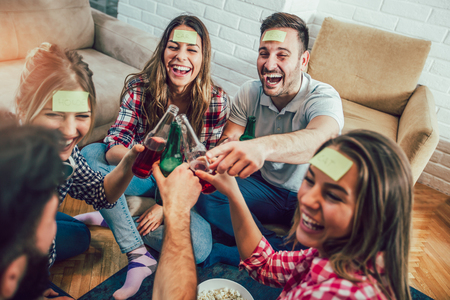 Happy friends playing game guess who and having fun at home Stock Photo