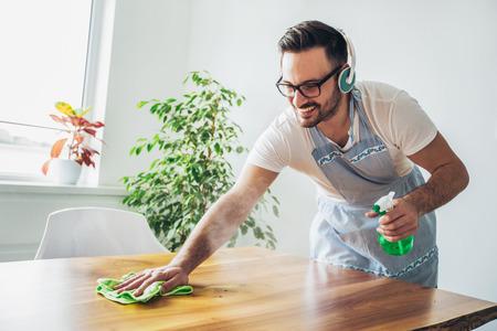 ラグとスプレーボトル洗剤でテーブルを掃除する若い笑顔の男