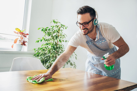 Young smiling man cleaning the table with a rag and spray bottle detergent