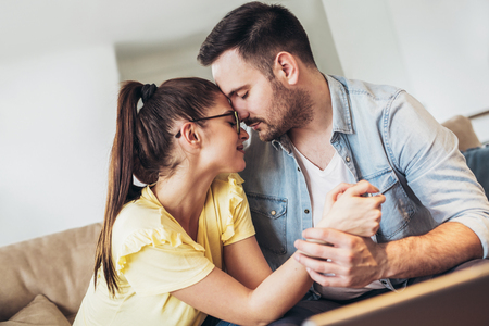 Loving young couple hugging and relaxing on sofa at home