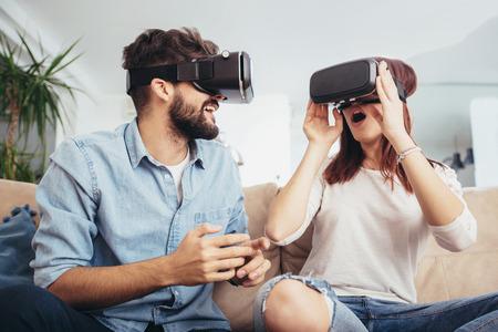 カジュアルな服を着た若い男女がバーチャルリアリティメガネを着用し、VRカメラ、テクノロジー、イノベーションコンセプトを通じて想像を見て示 写真素材