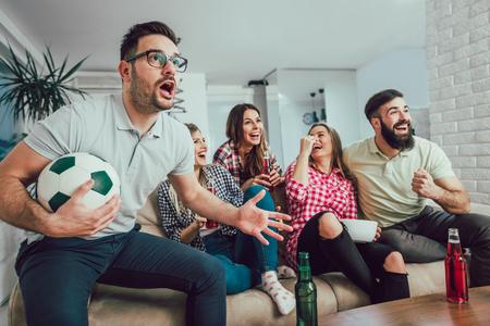 Szczęśliwi przyjaciele lub fani piłki nożnej oglądają piłkę nożną w telewizji i świętują zwycięstwo w domu. Koncepcja przyjaźni, sportu i rozrywki.