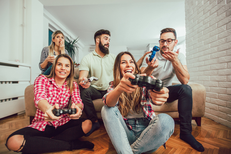 Group of friends play video games together at home, having fun.