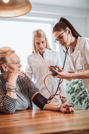Image of young medic taking blood pressure during home visit