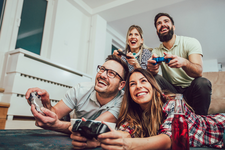 Grupo de amigos juegan videojuegos juntos en casa, divirtiéndose.