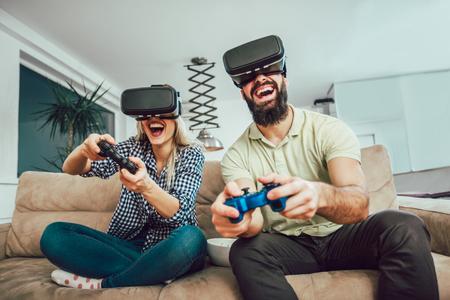 Amigos felices jugando videojuegos con gafas de realidad virtual: jóvenes divirtiéndose con la nueva consola de tecnología en línea