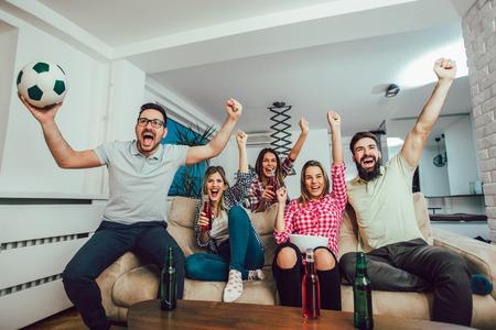 Amigos felices o fanáticos del fútbol que miran fútbol en la televisión y celebran la victoria en casa. Concepto de amistad, deportes y entretenimiento.