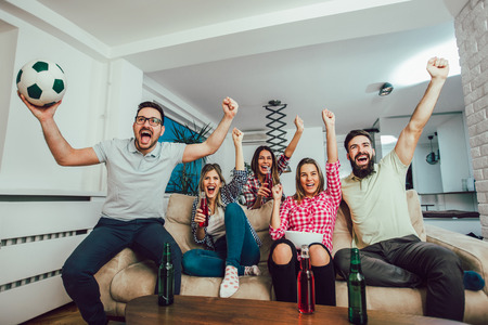 Happy friends or football fans watching soccer on tv and celebrating victory at home.Friendship, sports and entertainment concept. Stockfoto