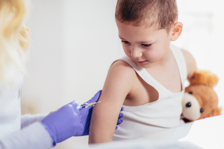 Doctor doing vaccine injection to a child, medicine, healthcare, pediatry and people concept Stock Photo