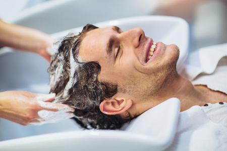 彼女のハンサムなクライアントに髪を洗う美容師。職場の理髪店。理髪店の男。