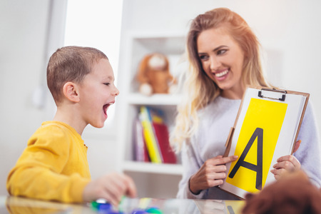 Speech therapist teaches the boys to say the letter A