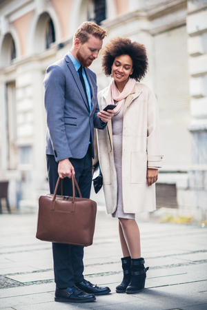 Two business people in an informal conversation in front of a business building, man using phone. Stock Photo