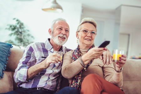 Happy senior couple with remote control watching tv on couch
