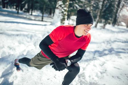 白い雪に覆われた場所で走る前に運動をするだけでスポーティなウェアを着ている若い男性