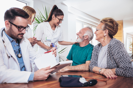 Senior Couple In Discussion With Health Visitor At Home. They talk about prescribed therapy Stock fotó
