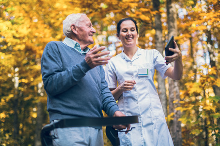 Smiling caregiver nurse and disabled senior patient in walker using digital tablet outdoor