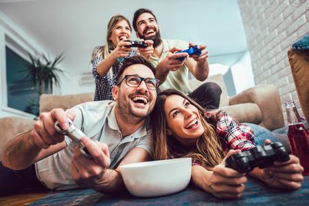 Un gruppo di amici gioca ai videogiochi insieme a casa, divertendosi. Archivio Fotografico