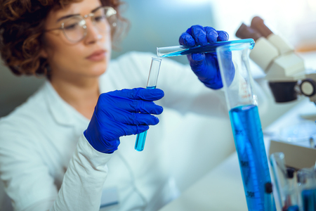 Young attractive female scientist in protective eyeglasses and gloves using test tube with blue liquid sample substance probe in the scientific chemical research laboratory Stock Photo