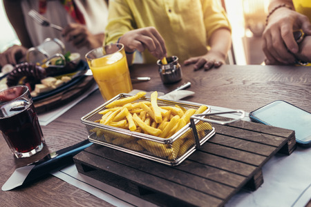 Children hands Picking French Fries on wood table in restaurant