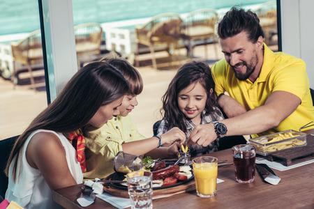 Padre y madre con hijos disfrutando de comida en el restaurante.