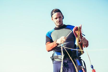 Kitesurfers on the beach prepare sport equipment for riding