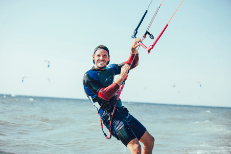 Kitesurfing Kiteboarding action photos man among waves quickly goes Stock Photo - 104962928