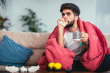 Young ill man drinking hot tea at home and watching tv