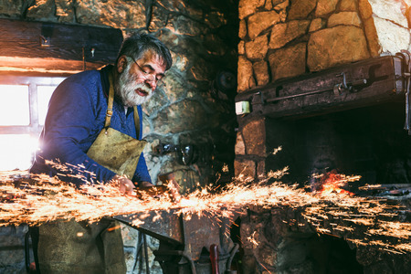 The blacksmith manually forging the metal on the anvil in smithy with spark fireworks