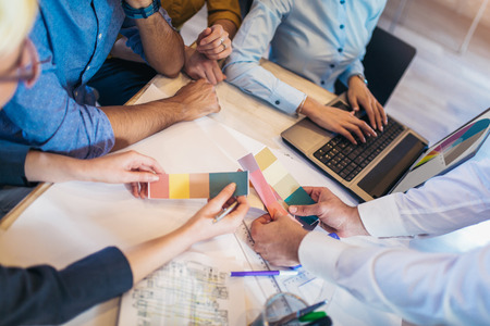 Creative team brainstorming in meeting room. Group of young adults sitting at the table with woman showing color palette to colleagues. Stock Photo