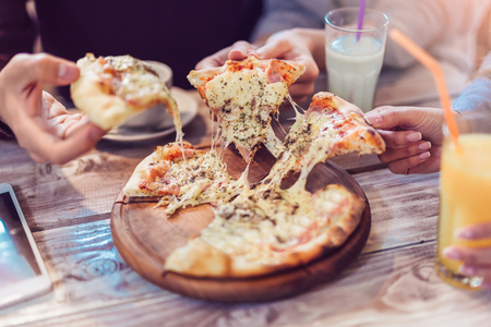 Eating Food. Close-up Of People Hands Taking Slices Of i Pizza. Group Of Friends Sharing Pizza Together. Stock Photo