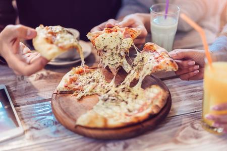 Essen essen. Nahaufnahme von Menschenhänden, die Scheiben von i Pizza nehmen. Gruppe von Freunden, die Pizza zusammen teilen. Standard-Bild