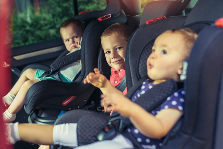 Three children in car safety seat - family, transport, safety, road trip and people concept Standard-Bild