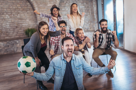 Happy friends or football fans watching soccer on tv and celebrating victory. Friendship, sports and entertainment concept. Stockfoto